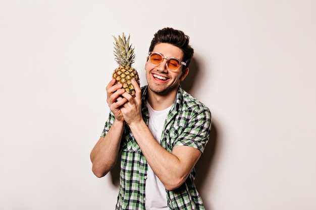 Charming man in checkered outfit and orange glasses smiles sweetly and holds pineapple.