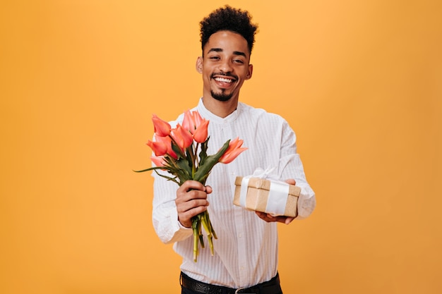 Charming man happily poses on orange wall and holds flowers, gift