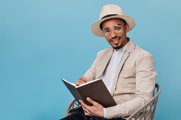 Charming man in hat and jacket holding book and looking into camera against blue wall