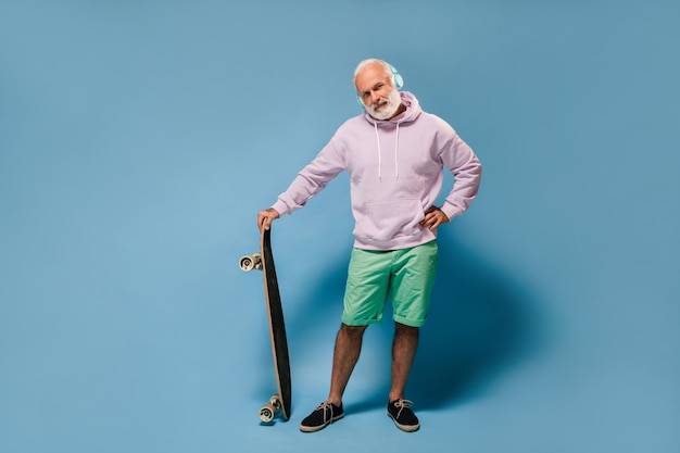 Charming man in hoodie and green shorts listening to music and holding skated board