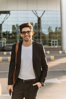 黒のスーツ、白のtシャツ、眼鏡をかけた魅力的な男性が笑顔でカメラをのぞき込む