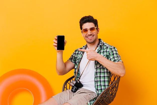 여름 옷을 입은 매력적인 남자는 검은 색 스마트 폰을 가리 킵니다. 풍선 동그라미와 오렌지 공간에 레트로 카메라와 함께 자에 포즈 쾌활 한 남자.