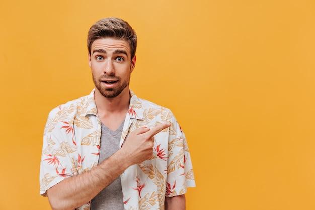 Affascinante uomo con acconciatura alla moda e barba allo zenzero in abiti freschi stampati leggeri che guarda nella telecamera e indica il posto per il testo
