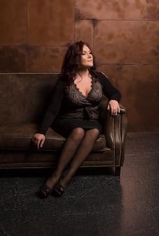 暗い部屋でポーズをとってファッショナブルなアパレルで魅力的な成熟したブルネットの女性
