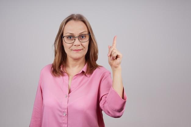 眼鏡をかけたピンクのブラウスの魅力的な成熟した実業家は、人差し指を上に向けて手を握ります