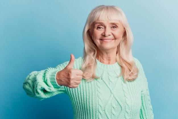 魅力的な成熟した女性は、青い背景で隔離の親指を表示します