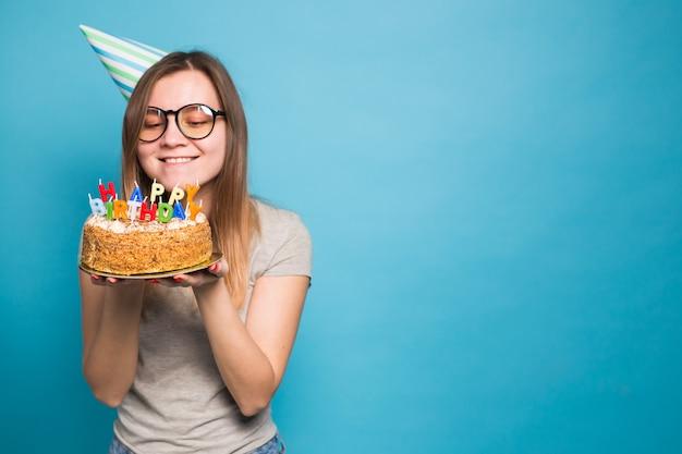 お誕生日おめでとうケーキを保持しているお祝いの紙の帽子の魅力的な陽気な狂気の若い女の子の学生