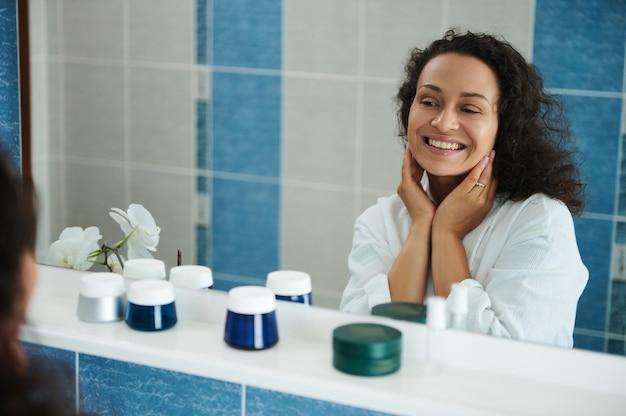 매력적인 중년 아프리카계 미국인 여성이 욕실 거울에 비친 자신의 모습을 보며 귀여운 미소를 짓고 있습니다.