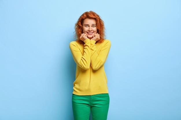 青い壁に向かってポーズをとる波状の赤い髪を持つ魅力的なミレニアル世代の女性