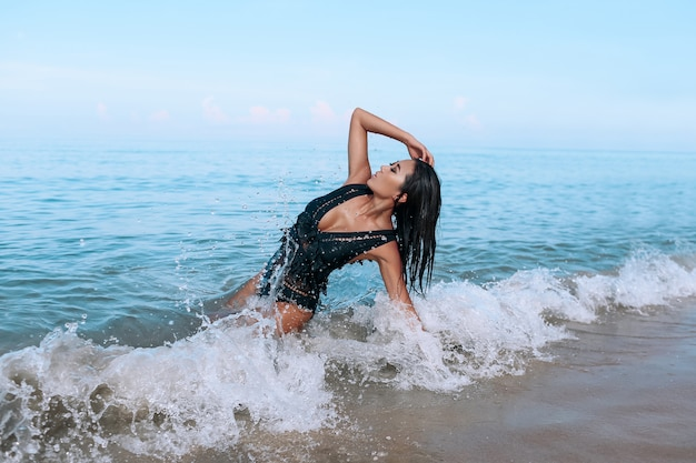 Charming miss in a stylish black swimsuit and bright makeup lies and relaxes beach. leisure and travel