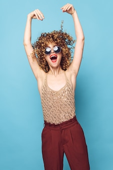 Charming model curly hair dark glasses red lips fashionable clothes red pants blue isolated background