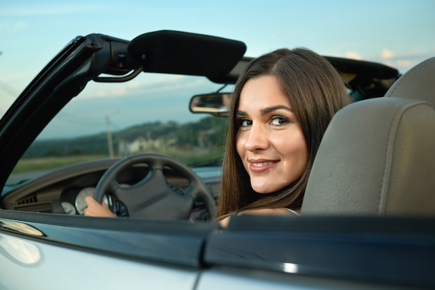 Charming model smiling and driving cabriolet.