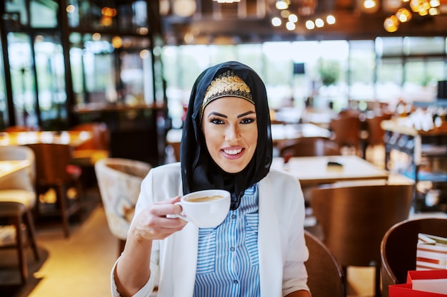 Charming modern smiling muslim woman sitting in cafe and holding cup of coffee.