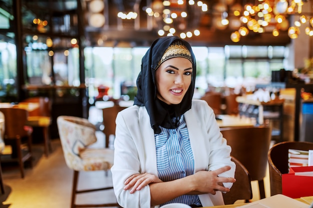 Charming modern smiling muslim woman with scarf sitting in cafeteria with hands folded
