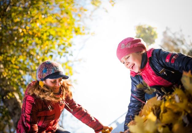 화창한 날 산책하는 동안 매력적인 엄마와 쾌활한 딸이 공원에서 노란 단풍잎으로 놀고 있습니다. 가족 시간과 재미있는 전통의 개념