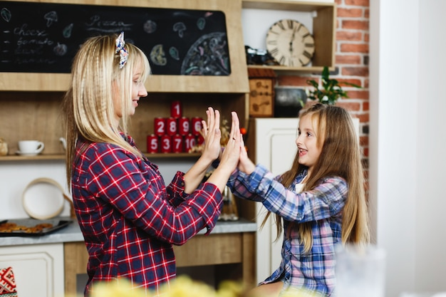 Charming mom and daughter have fun in a cosy kitchen