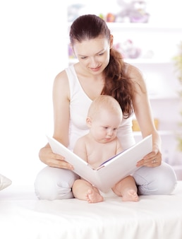 Очаровательная мама читает книгу своему малышу