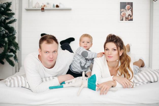 작은 귀여운 아들이 침대에 함께 누워 정면을보고 겨울에 스튜디오에서 포즈를 취하는 매력적인 어머니와 아버지