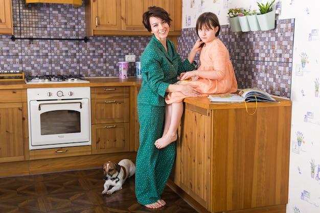魅力的な母親と彼女の小さな娘は家にいます