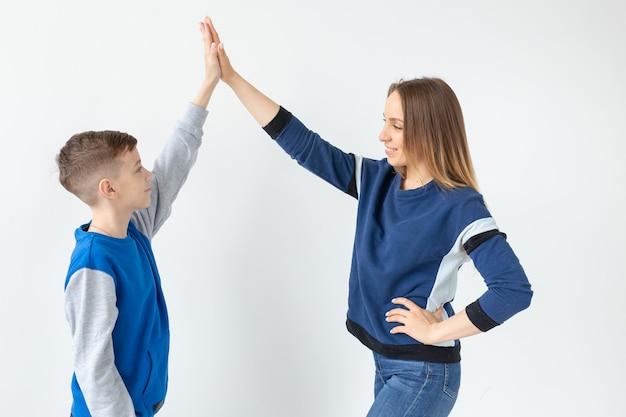 Очаровательные мама и сын хлопают друг друга в ладоши, наслаждаясь идеальным переездом в новую квартиру. в