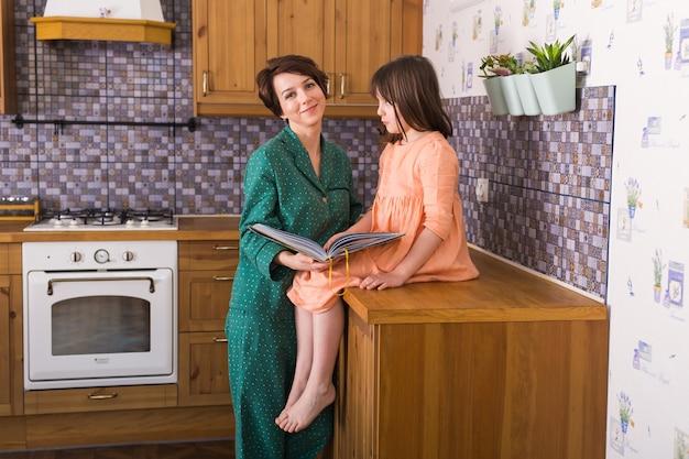 魅力的な母親が自宅でかわいい娘に本の画像を見せています