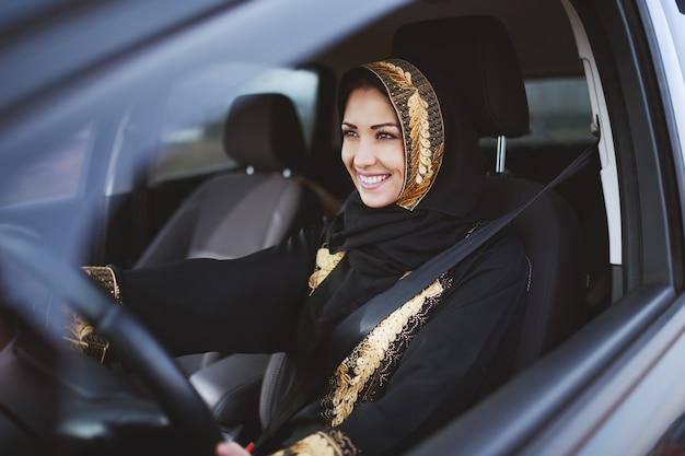 Очаровательная мусульманская женщина, одетая в традиционную одежду, держа одну руку на руле, а другой, показывая большой палец вверх.