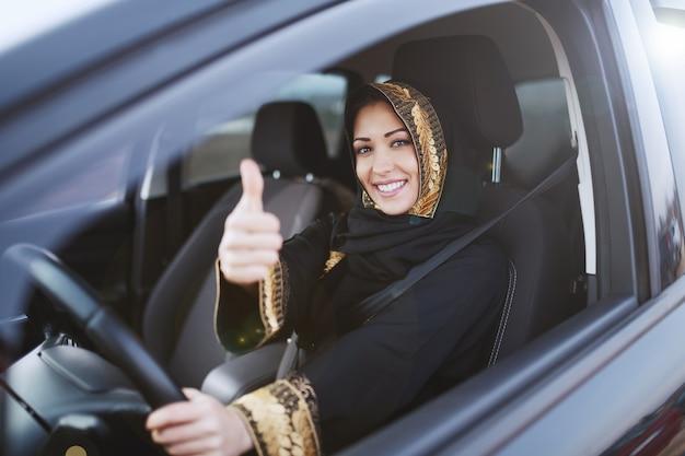 魅力的なイスラム教徒の女性は、ハンドルを片手で握りながら親指を立てた伝統的な服を着ています。