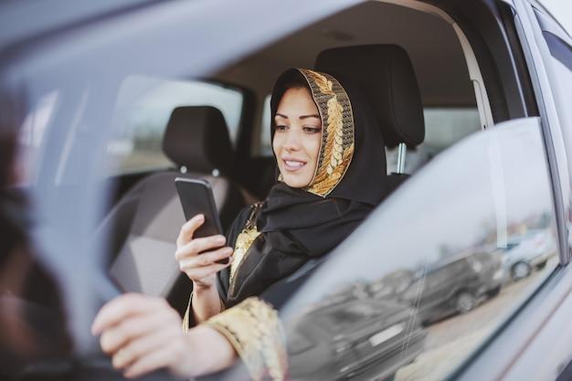 車でスマートフォンを使用して伝統的な摩耗に身を包んだ魅力的なイスラム教徒の女性。