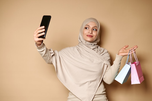 Charming muslim woman holding blue and pink bags in one hand and a smartphone in the other, making selfie.