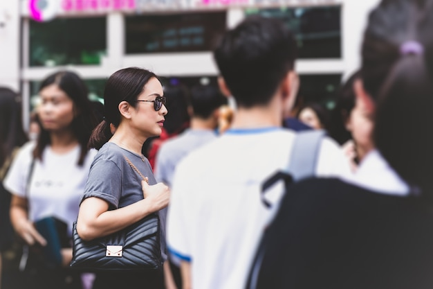 Charming mysterious woman with sunglasses standing outside building in a crowd.
