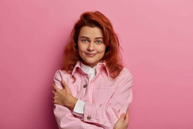 Affascinante donna naturale si abbraccia, ha un'alta autostima, indossa una giacca alla moda in denim rosa, fossette sulle guance, capelli voluminosi