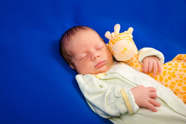 Charming newborn baby boy sleeping on a blue blanket with little toy