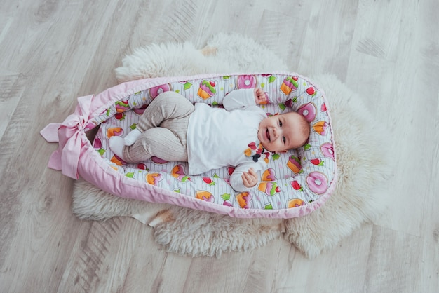 Charming newborn baby in a pink cradle