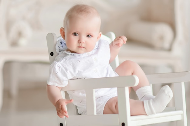 Charming newborn boy sits on the chair in the studio