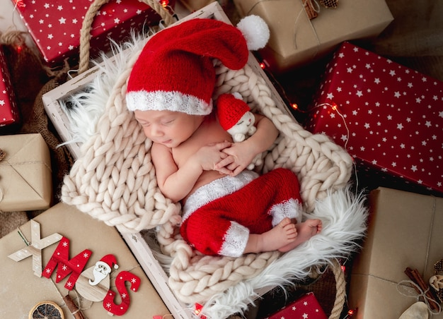 Очаровательный новорожденный спит между рождественскими подарками