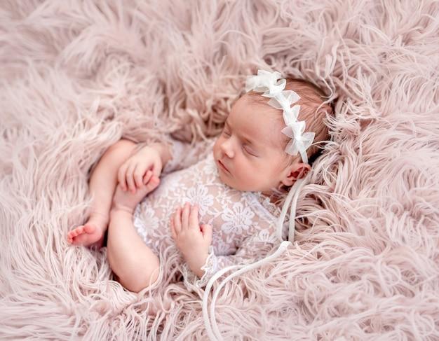 魅力的な新生児のレースのスーツとdiademを着て