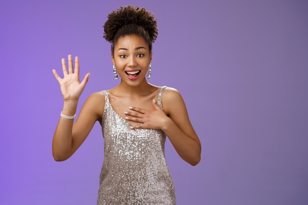Charming nice young african-american elegant woman meet familiar person greeting raise hand waving press palm chest smiling broadly say name, swearing tell truth, standing promise not lie.