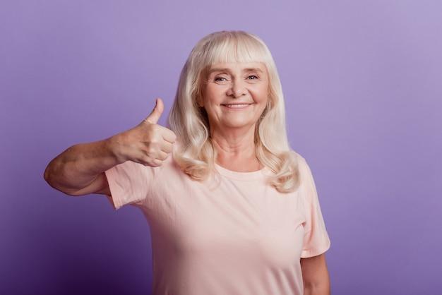 魅力的な老婦人は紫色の背景に分離された親指を表示します