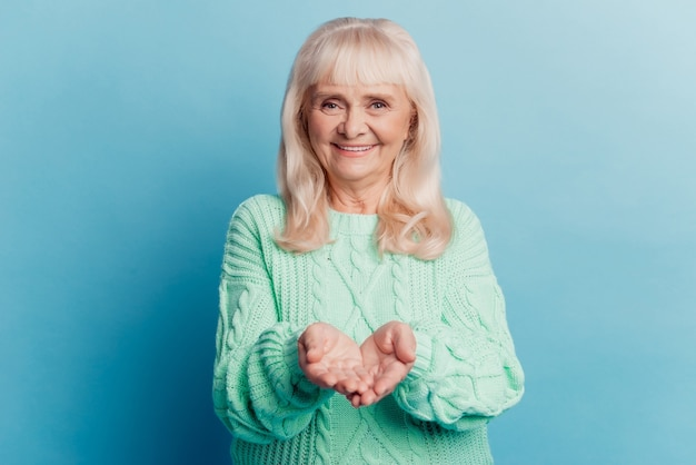 Charming old woman hold copy space on palm isolated on blue background