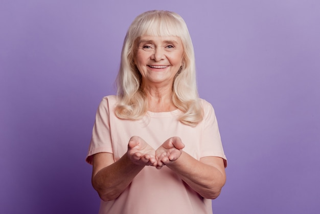 Charming old woman hold copy space on palm isolated on violet background