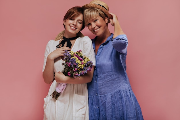 Charming old woman with short blonde hair in blue dress and straw hat smiling with girl in white clothes with beautiful flowers on pink background.