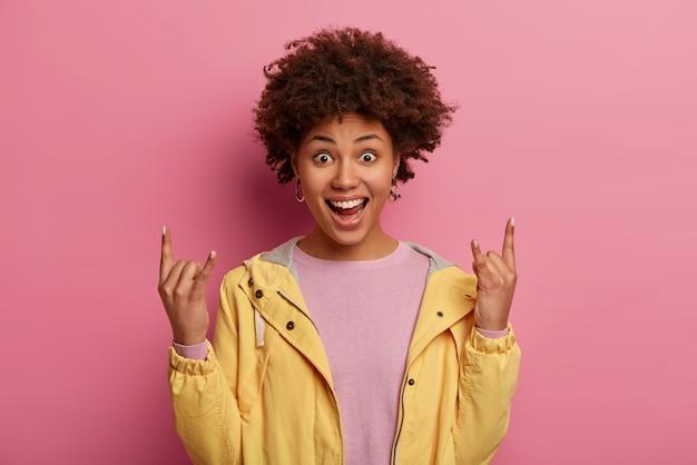 Affascinante ragazza femminile felicissima fa il gesto del rock n roll, si sente spensierata e felice, ascolta la musica preferita