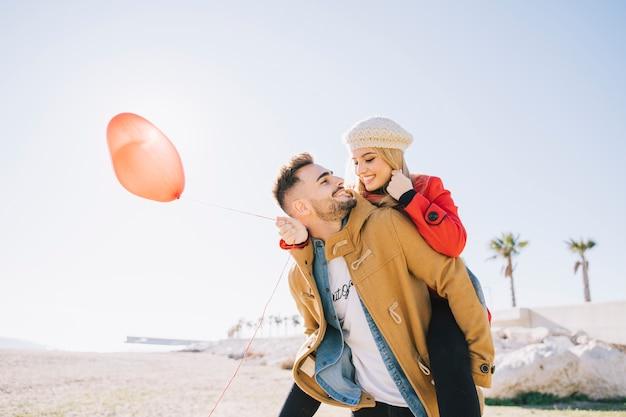Persone affascinanti con palloncino rilassante sulla spiaggia
