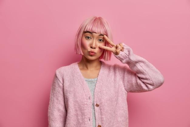 Affascinante ragazza dai capelli rosa mostra il gesto di vittoria, fa un segno di pace con le dita sul viso, ha un'espressione gentile e sicura, indossa un maglione caldo
