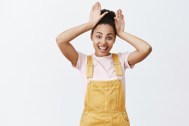 Очаровательная игривая афроамериканка с зачесанными волосами в желтом комбинезоне, держащая ладони за голову и широко улыбаясь, имитирующая кролика или щенка с длинными ушами над серой стеной