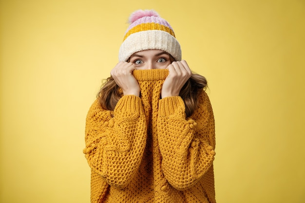 Очаровательная игривая харизматичная девушка, пряча лицо, натянула воротник свитера, расширила глаза, удивилась счастливой ...
