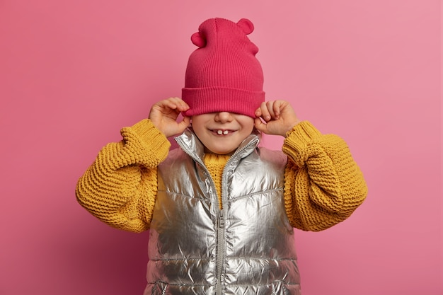 Charming playful small kid hides face with hat, dressed in warm sweater and vest, enjoys childhood, poses indoor against pastel rosy wall, has two teeth stick out. casual style. happy emotions concept