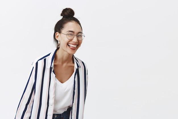 Affascinante donna giocosa che ride su uno scherzo divertente, in piedi in occhiali e abbigliamento alla moda