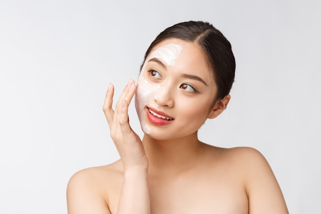 Charming pleasant woman applying cream on half face