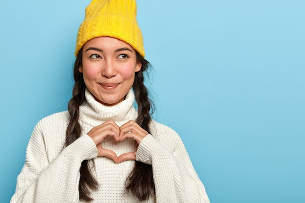 Charming pleased young asian woman makes heart sign, confesses boyfriend in love, has pleased face expression, looks aside, wears yellow hat and jumper